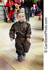 Little boy in military uniform on holiday victory day