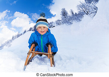 Little boy in mountains slide on sledge
