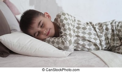 Little boy in pajamas lying asleep on the bed