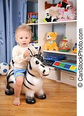 little boy in playroom on toy zebra