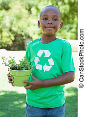 Little boy in recycling tshirt holding potted plant on a ...