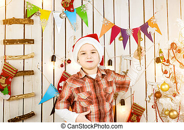 little boy in red hat holding christmas tree toy