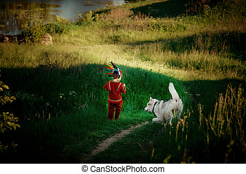 little boy in  red suit Indian plays with  dog husky runs on the field and trails