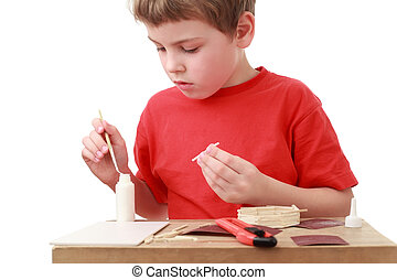 little boy in red T-shirt crafts at small table, boxcutter,...