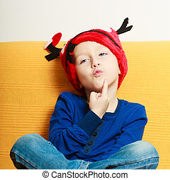 little boy in red winter reindeer hat at home