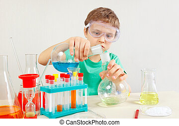 Little boy in safety goggles studies chemical practice in laboratory