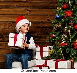 Little boy in Santa hat with gift box under christmas tree in wooden house interior