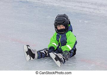 Little boy in skates sitting on ice