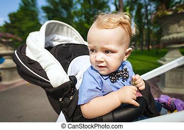 little boy in stroller outdoors