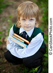 boy in suit holding four books
