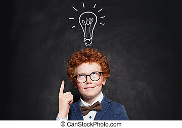 Little boy in suit pointing at lightbulb on blackboard background. Brainstorming and idea concept