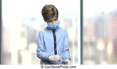 Little boy in surgical mask puts on gloves. Boy want to be a...