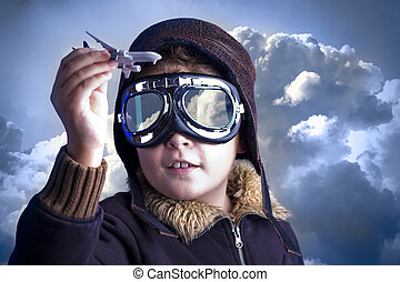 Little boy in the pilot`s hat. Boy as an old style pilot holding a toy airplane