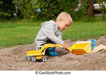 Little boy in the sandbox.