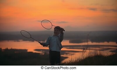 Little boy in the sunset is played with rackets for...