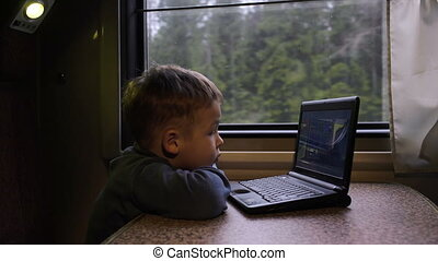 Little boy in the train watching video on laptop