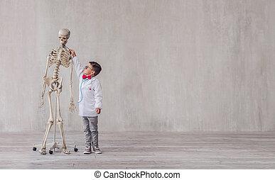 Little boy in uniform with a skeleton