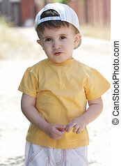 Little boy in yellow shirt and cap