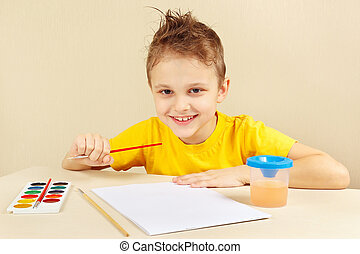Little boy in yellow shirt going to paint colors