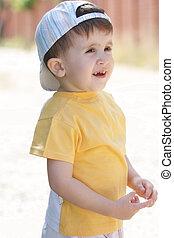 Little boy in yellow shirt looking sideways