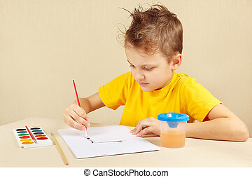 Little boy in yellow shirt painting colors