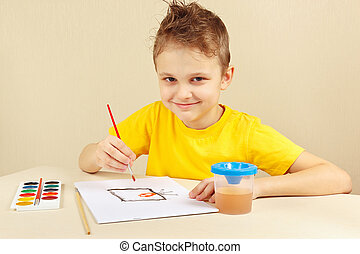 Little boy in yellow shirt painting with watercolors