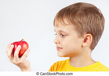 Little boy in yellow shirt with red apple