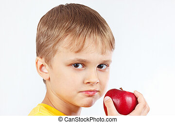 Little boy in yellow shirt with ripe red apple