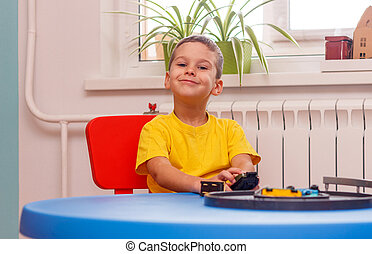 Little boy in yellow t-shirt playing with cars and toys at home, indoor