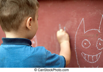 Little boy is drawing with chalk