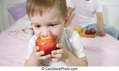 Little boy is eating apple in parent's bedroom. His parents...