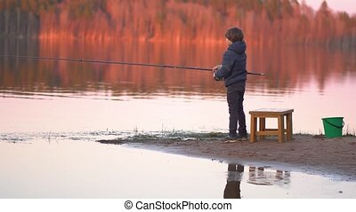 Little boy is fishing at sunrise on the lake - Child with ...