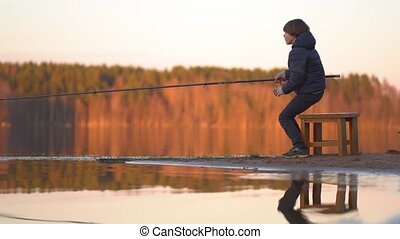 Little boy is fishing at sunset on the lake - Little boy is ...