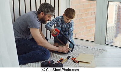 Little boy is focused on sawing piece of wood with hand saw...