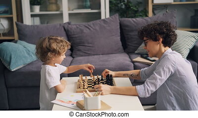 Little boy is happy after chess game celebrating and doing...