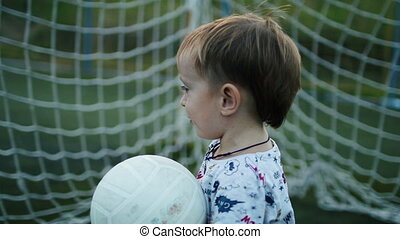 Little boy is holding the ball in his hands on the football field