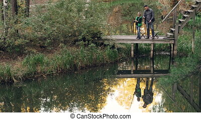 Little boy is learning to catch fish from his father standing together on wooden pier and talking holding fishing rods. beautiful lake and forest are visible.