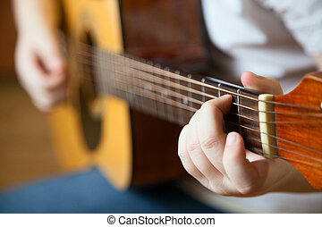 Little boy is playing the guitar