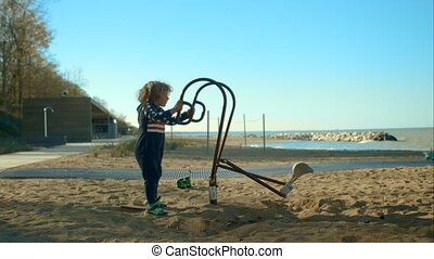 Little boy is playing with an excavator on the sandy beach