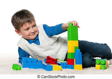Little boy is playing with blocks