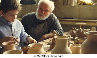 Little boy is playing with clay sitting with his grandparent at table in home pottery studio. Grandfather is talking to curious child, boy is enjoying new hobby.