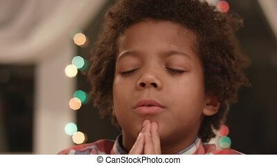 Little boy is praying to God. Close-up face of obedient...