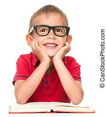Little boy is reading a book