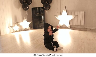 Little boy is sitting on the Studio floor against a background of glowing stars.
