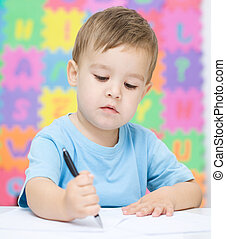 Little boy is writing on his copybook