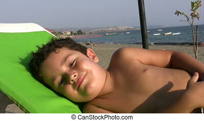 little boy istenning to the seashel