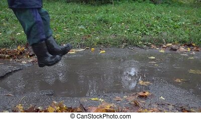 Little boy jumping in muddy puddle, slow motion 250 fps