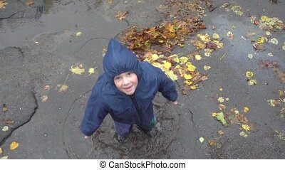 Little boy jumping in muddy puddle, slow motion