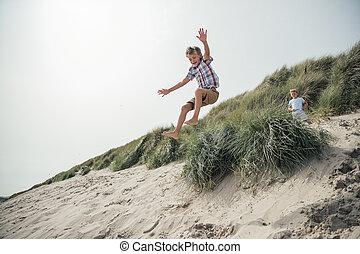 Little Boy Jumping Over a Sand Dune