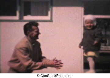 A little boy jumps into his dad's arms while playing in the back yard. (Scan from archival 8mm film)